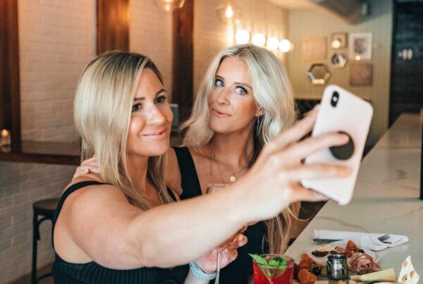 blond girl taking selfie with friend